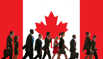 International workers walking in front of the Canadian flag