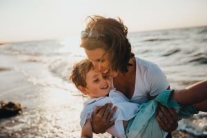 smiling mother holding son at the beach