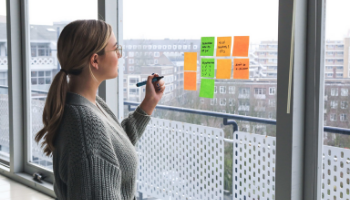 blond female worker standing in front of a window and writing on sticky notes