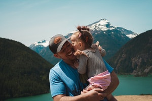 toddler kissing father on cheek