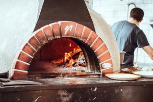 Pizza maker beside a brick oven