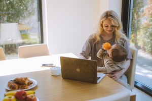 Canadian mother holding baby infront of laptop