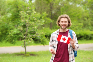 Canadian male student holding a canada flag