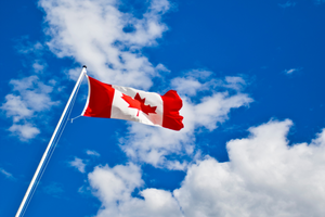 Canada flag waving in the bright blue sky