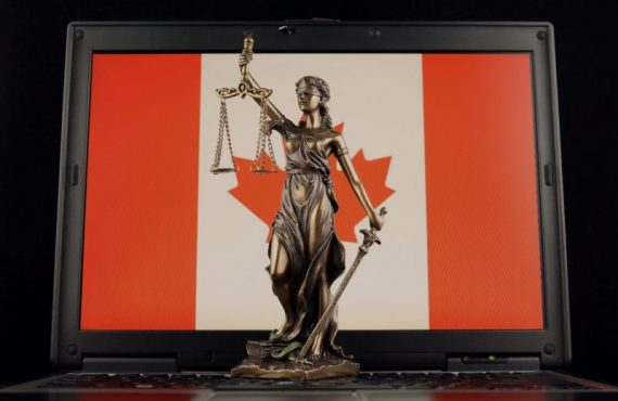 Lady justice statute in front of a laptop with Canadian flag background