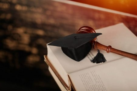 Graduation cap and gavel on a book